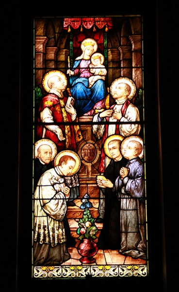 """This stained glass window, found in the school's Holy Name Chapel (small chapel) depicts Mary, Queen of the Society of Jesus, with St. Ignatius Loyola (left) and St. Francis Xavier (right) standing near her throne. Also depicted are, from left, St. Alphonsus Rodriguez and the three """"Saints of Youth"""" — Aloysius Gonzaga, John Berchmans, and Stanislaus Kostka."""