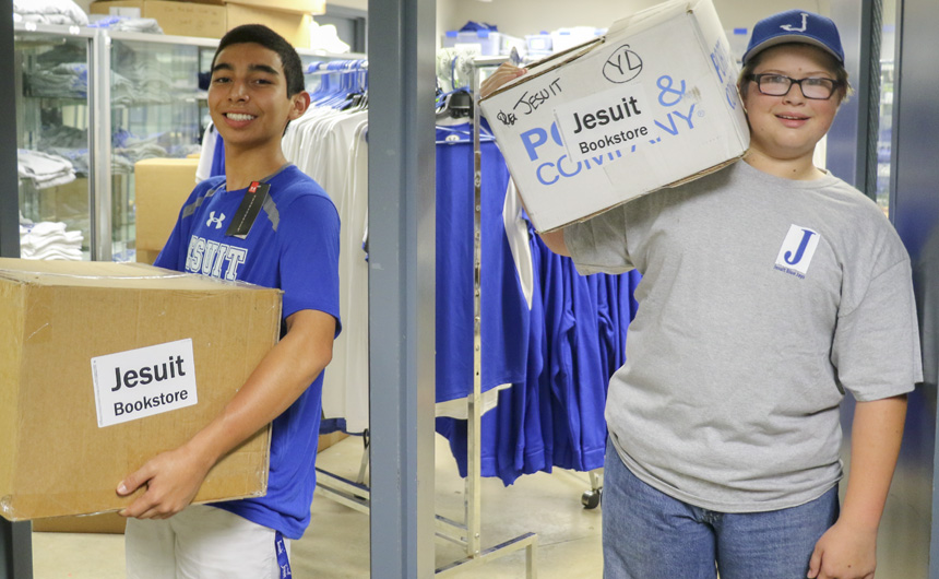 Rising junior Richard Montoya and rising pre-freshman Anthony Guernsey open the doors at the entrance of the Blue Jay Shop as they haul in the last few boxes.